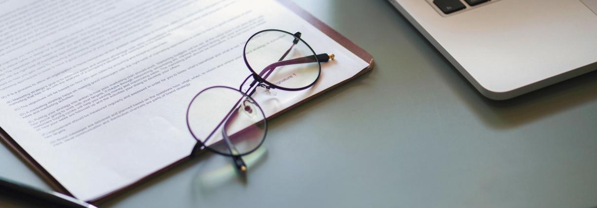 Brille auf einem Dokument zwischen einem Laptop und einer Brille